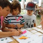 Dvoje djece i dvije odrasle osobe slažu šišmiša od papira.