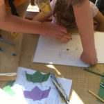 Odrasla osoba usmjerava djetetovu ruku dok crta šišmiša.