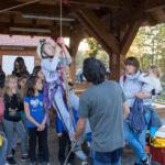 Dijete se penje po užetu koristeći opremu za penjanje. Na glavi mu je zaštitna kaciga. Asistira mu odrasla osoba, a promatraju ga okupljena djeca i odrasli.