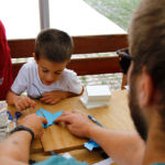 Odrasla osoba pomaže djetetu napraviti šišmiša od papira.