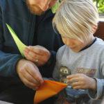 Dijete i odrasla osoba slažu svatko svoj origami.
