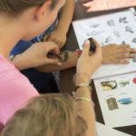 Žena uz pomoć plastične šablone s obrisom šišmiša i spužvice s bojom oslikava ruku djeteta.