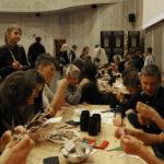 Djeca sjede za nekoliko stolova i stoje pored njih, razgovaraju i izrezuju papire škarama.