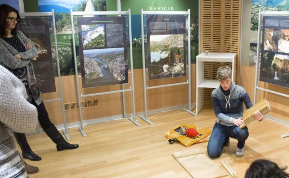 Predavačica pokazuje model drvene kućice za šišmiše ljudima koji ju okružuju.