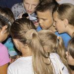 Grupa djece okupila se oko istraživačice koja u ruci drži ulovljenog šišmiša.