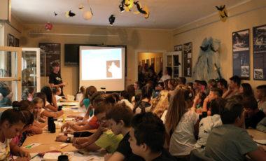 Mlada žena drži predavanje u prostoriji punoj djece.