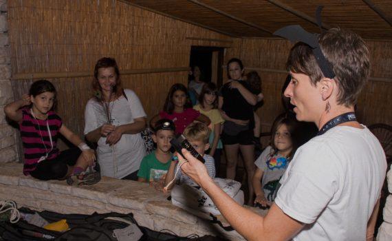 Žena drži ultrazvučni detektor u podignutoj ruci. Drugi ljudi su okupljeni uz nju i promatraju je.