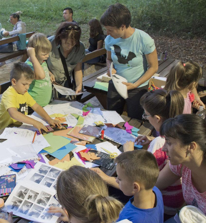 Djeca i odrasli za stolom punim raznobojnog papira za slaganje origamija, uputa za slaganje i već složenih šišmiša, te drvenih bojica i drugog pribora.
