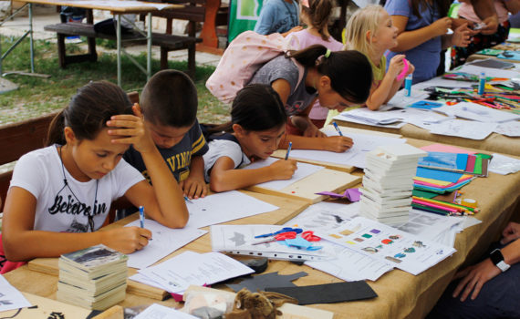Djeca sjede za stolovima na kojima su papiri, drvene bojice, škare i drugi pribor. Neka rješavaju kvizove, neka crtaju.