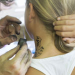 Muškarac uz pomoć plastične šablone s obrisom šišmiša i spužvice s bojom oslikava vrat djevojčice.