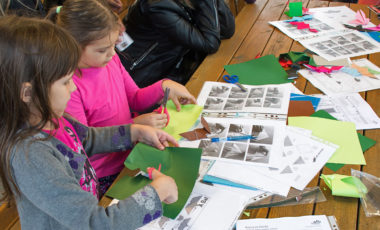 Dvije djevojčice škarama izrezuju likove iz papira u boji. Na stolu pred njima rasprostrti su drugi papiri u boji i upute za izradu origami šišmiša.