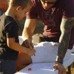 Dječak crta šišmiša. Odrasli muškarac mu pomaže.