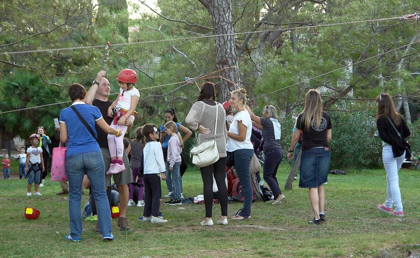 speleolog priprema dijete za isprobavanje spuštanja po užetu; ostali okupljeni posjetitelji promatraju njihovu aktivnost