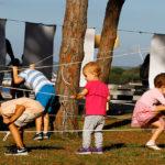Djeca se provlače ispod i prelaze preko užeta razapetih među drvećem.