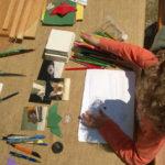 Dijete crta za stolom na kojem su papiri, pribor za crtanje i ploče za igranje memoryja s fotografijama šišmiša.