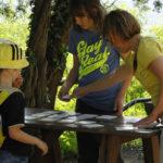 Žena i dvoje djece za stolom po kojem su raširene pločice za igranje igre memory.