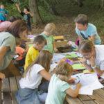 Za stolovima punim raznobojnog papira za slaganje origamija, papira za crtanje, drvenih bojica i drugog pribora djeca se igraju pod nadzorom odraslih.