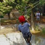 Dječak u speleološkoj opremi se spušta niz razapeto uže prema muškarcu koji ga dočekuje na drugom kraju užeta.