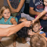 Odrasla osoba u rukama drži sklupčanu mrežu. Okupljena djeca ju dodiruju.