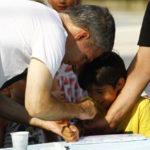 Muškarac oslikava djetetovu ruku.