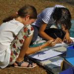 Dvije djevojčice čuče i crtaju.
