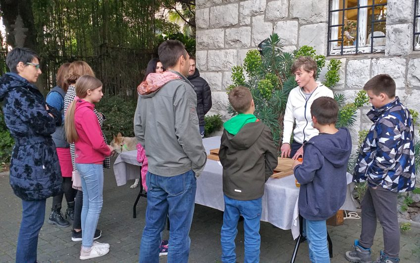 Posjetitelji okupljeni oko stola gdje im predavačica pokazuje drvenu kućicu.