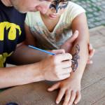 mladić slika šišmiša na ruci djeteta