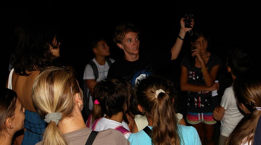Mlada žena drži bat detector (uređaj za bilježenje ultrazvučnog glasanja šišmiša) podignut u ruci pred posjetiteljima okupljenim oko nje, te im demonstrira rad uređaja.