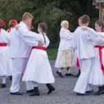 Žene i muškarci plešu odjeveni u tradicionalne bijele nošnje. Djeca ih promatraju sa strane.