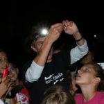 Istraživačica drži šišmiša podignutog iznad glave i pokazuje ga djeci okupljenoj oko nje.