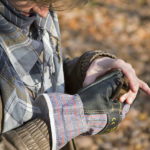 Istraživačica drži šišmiša u rukama i pregledava ga.