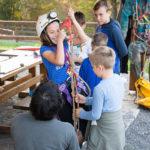 Djevojčica s kacigom na glavi se penje po užetu uz pomoć opreme za penjanje. Asistira joj odrasla osoba. Promatraju ih druga djeca okupljena oko njih.