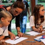 Dvoje djece i roditelj crtaju za stolom.