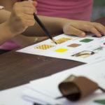 Papir sa šišmiš kvizom leži na stolu. Pridržavaju ga dječje ruke i drvenom bojicom zaokružuju odgovore.