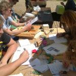 Ljudi sjede za stolom punom listova papira, olovki, složenih origami šišmiša i drvenih elemenata za izradu kućice za šišmiše.