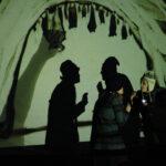 Dvije osobe stoje ispred pozadine na kojoj je projiciran crtež pijeskom koji prikazuje šišmiše na stropu spilje.