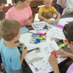 Djeca sjede za stolom punim papira i zajedno s odraslom osobom slažu origami šišmiše.