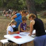 Djeca za stolom slažu figure od papira, u prisustvu odraslih.