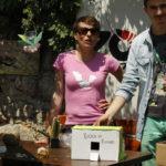 Žena i muškarac stoje iza štanda na kojem su prikazana skloništa za kukce, jedno od kartonske kutije a drugo od suhog granja.
