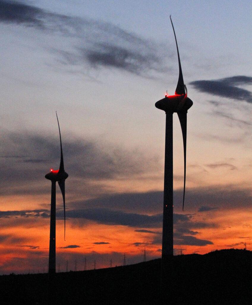 Dva vjetroagregata, u pozadini nebo crveno od sunca na zalazu.