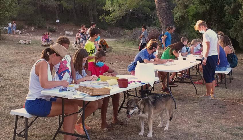 Djeca i odrasli sjede za stolovima, crtaju i slažu figure od papira.